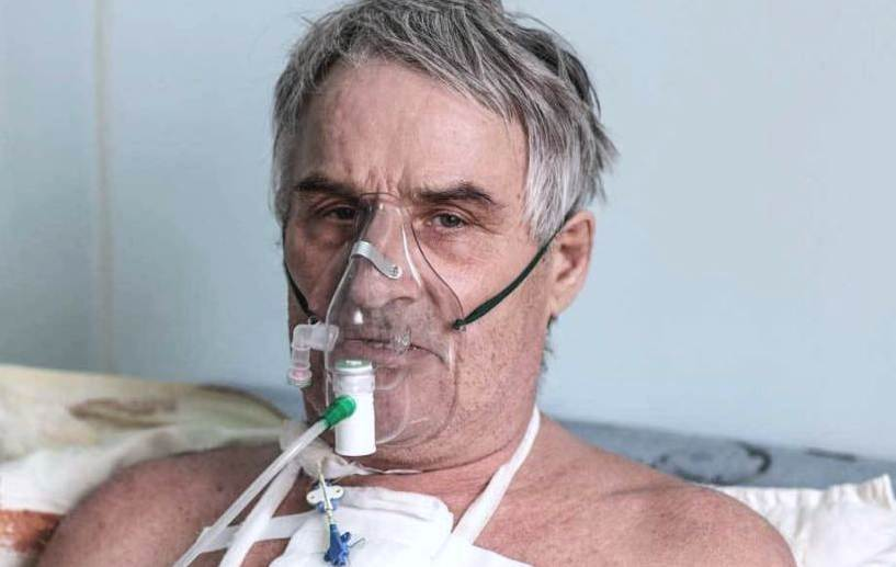 Person with oxygen mask in a hospital ward